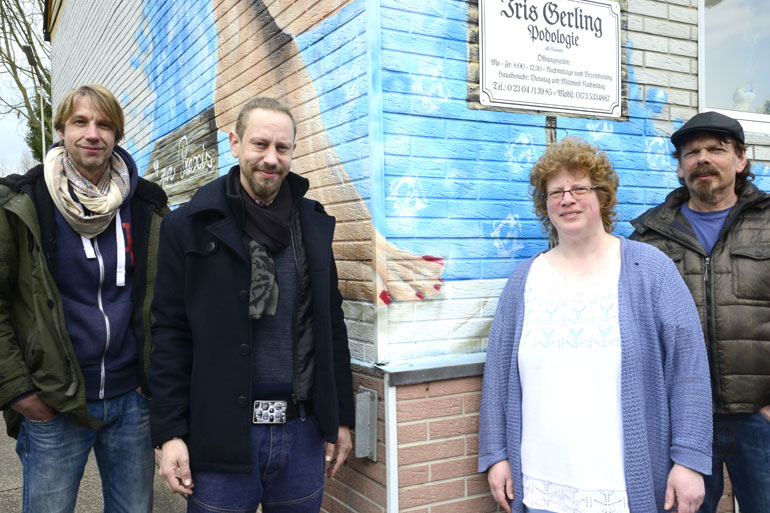 Iris Gerling mit dem Projektkoordinator Detlef Kraas (r.), Projektbgeleiter Volker Kranefeld (l.) und dem Graffiti-Künstler Roberto Trementino vor ihrer Praxis in der Hagener Straße 100.